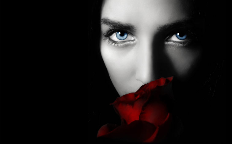Woman smelling rose, staring with seductive eyes.