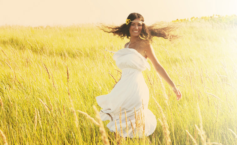 Woman dressed in white swirling in a golden field