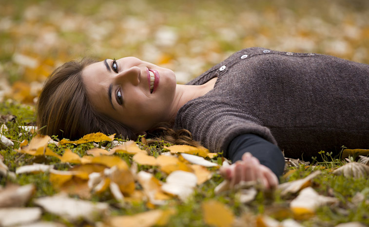 woman lying on ground with arm outstretched towards you.